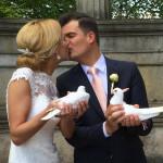 Glückliches Hochzeitspaar mit Tauben in der Hand küssen sich. Tolle Brautfrisur vom Hochzeitsfriseur Dresden.