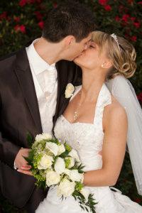 Braut mit Hiochsteckfrisur, sinnlicher Kuss eines Brautpaares