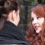 Josi mit Hochsteckfrisur, und brauenen Locken im Gespräch mit Freundin