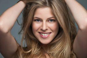 natürlich blonde Haare mit Strähentechnik von Coiffeur Lauda Blond-Experte in Dresden, Glückliche Blondine mit Händen im Haar