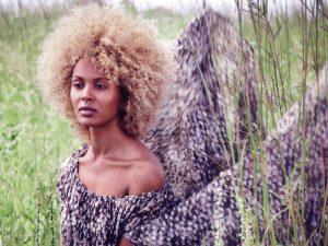 Haare blond färben - Natürlichkeit bewahren, hier farbige junge Frau mit blonder Lockenpracht und schönem Kleid im Gras